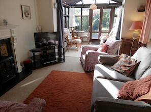 A sitting room with gas fireplace, television, video and DVD, stereo, adjoining conservatory leading to the garden.